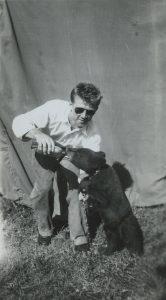 Black and white photo of a young Bingo Hauser bottle feeding a black bear cub