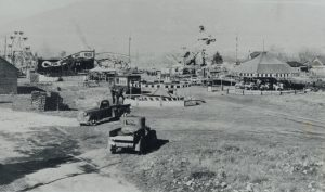 Black and white photo of a carnival midway, two trucks are in front, there is a lot of different areas set up including a Fun House
