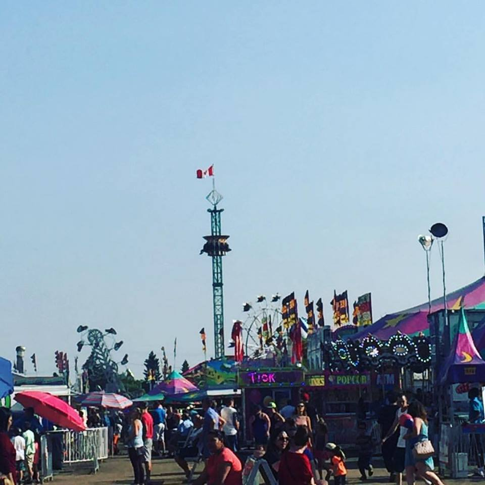 A carnival midway with many rides and concessions set up, seen in the distance are the Zipper, Super Shot and Ferris wheel rides, a carousel can be seen in front