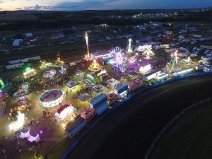Bird's eye view of carnival midway at dusk, the lights shine bright from a distance