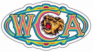 The logo for West Coast Amusements, WCA in a horizontal oval shape with colours blue, pink, yellow and purple. A roaring lion head illustration is in the middle of the C