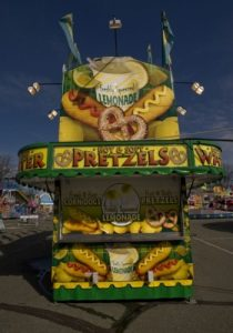 A hot and soft large pretzel concession stand, also advertising corn dogs and lemonade with colourful graphics