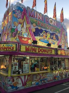 A concession stand for mini donuts, also advertising hot and cold drinks, the stand has colourful graphics and cartoons all over, the sign is lit up