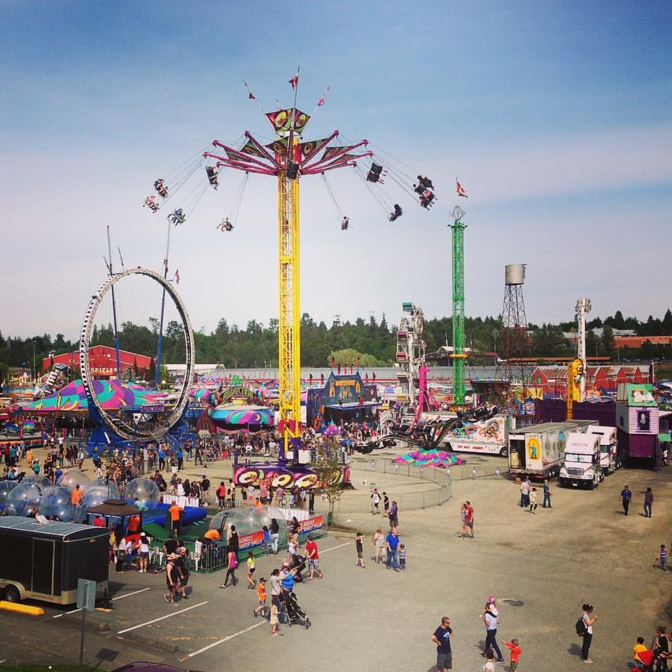 A large view of a carnival midway set up in a parking lot, the Vertigo ride is featured in the middle