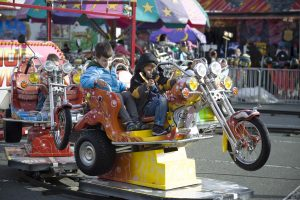 Two young boys riding a kiddie ride that is a motorcycle on a track at a carnival midway