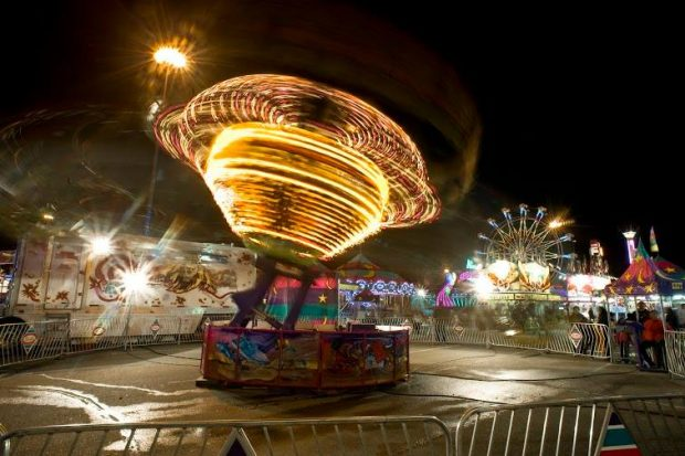 A carnival midway at night, featuring a rapidly spinning lit up ride, a Ferris wheel can be seen in the background