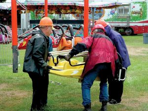 Four men wearing hard hats are lifting and moving a carnival ride bucket