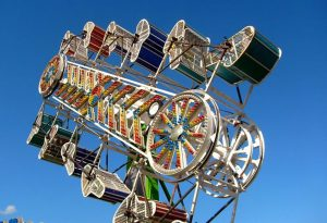 Zipper carnival ride, has different coloured ride buckets on both vertical sides, the buckets spin around as the ride moves