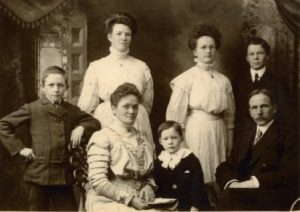 A family of seven grouped together wearing formal clothes.