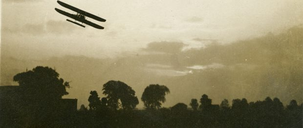 A silhouetted bi-plane flying above trees.