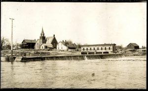 Petit barrage sur une rivière, devant quelques bâtiments.
