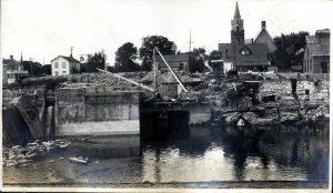Travaux de construction sur une rivière, avec une église à l'arrière-plan.