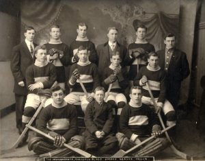 A group of men seated and standing in three rows, posing for a team photo.