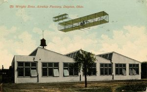 Bi-plane flying above buildings.
