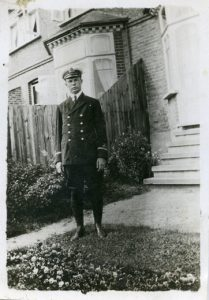 A man in a pilot's uniform standing in front of a wooden fence.