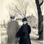 A man in military uniform and woman in a fur coat standing in the snow. Trees and homes in the background.