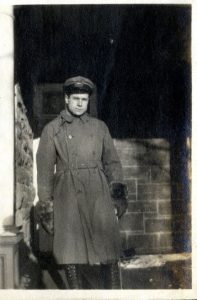 Man standing on a veranda wearing a military uniform.