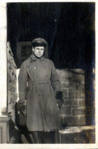 Man standing on a veranda wearing a military uniform.