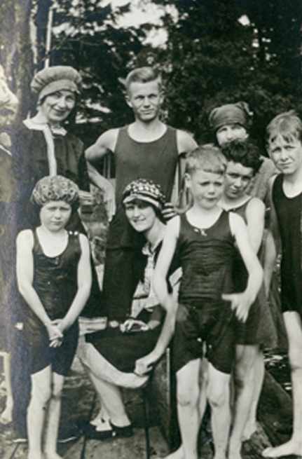 A group of mostly children standing on a dock in bathing suits.