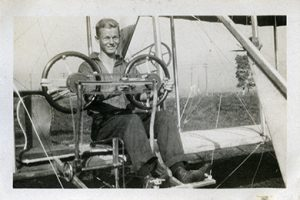 A man sitting in the pilot's seat of a bi-plane.