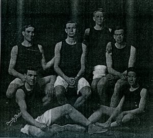 Six men grouped together wearing basketball uniforms.