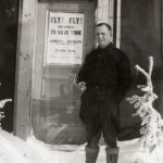 A man standing in the snow in front of a door.