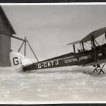 Two pilots dressed in flying gear in front of an open cockpit plane of a bi-plane on skis, in winter, in front of a hangar.