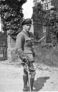 A man dressed in a military uniform standing casually in front of an iron fence outside of a house.