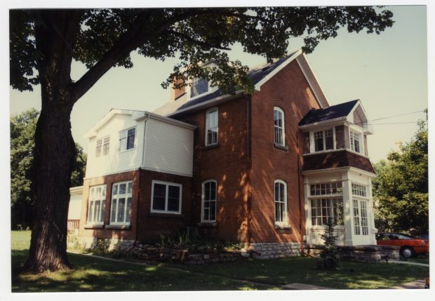 A large two and a half storey red brick house with a glassed in veranda.
