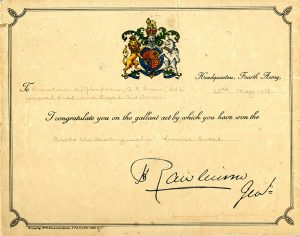 Coloured certificate with a coloured coat of arms at the top, scroll work around the edges and writing in the centre.