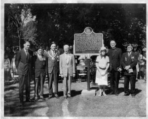 A group of people standing in front of a large, raised plaque.