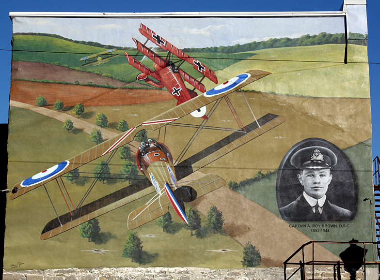 Illustration of two British First World War bi-planes and a German tri-plane in a dog fight over open fields with a man's portrait in the lower right corner.