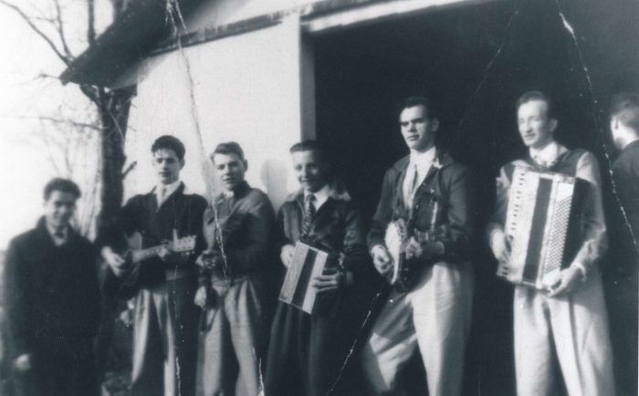 Black and white photograph of a seven-man band posing in front of a sugar shack.