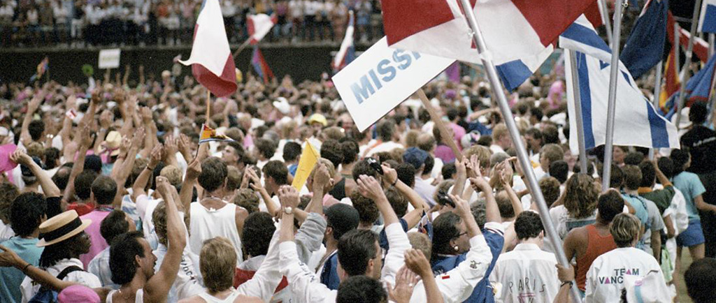 Crowds of athletes and other participants, waving various national flags at the Celebration '90 Opening Ceremony.