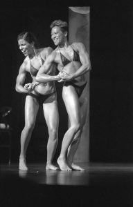 Black and white photo of gold medal winners in the Physique Female Pairs category, Americans Kitty Tsui and B.C. Cliver, assume a Side-Chest pose on stage at the Orpheum Theatre.