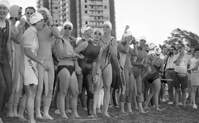 Black and white photo of women Triathlon athletes in swim suits, googles, and bathing caps, crowded together at the start line on the beach at English Bay preparing for the 1.5K swim portion of the event.