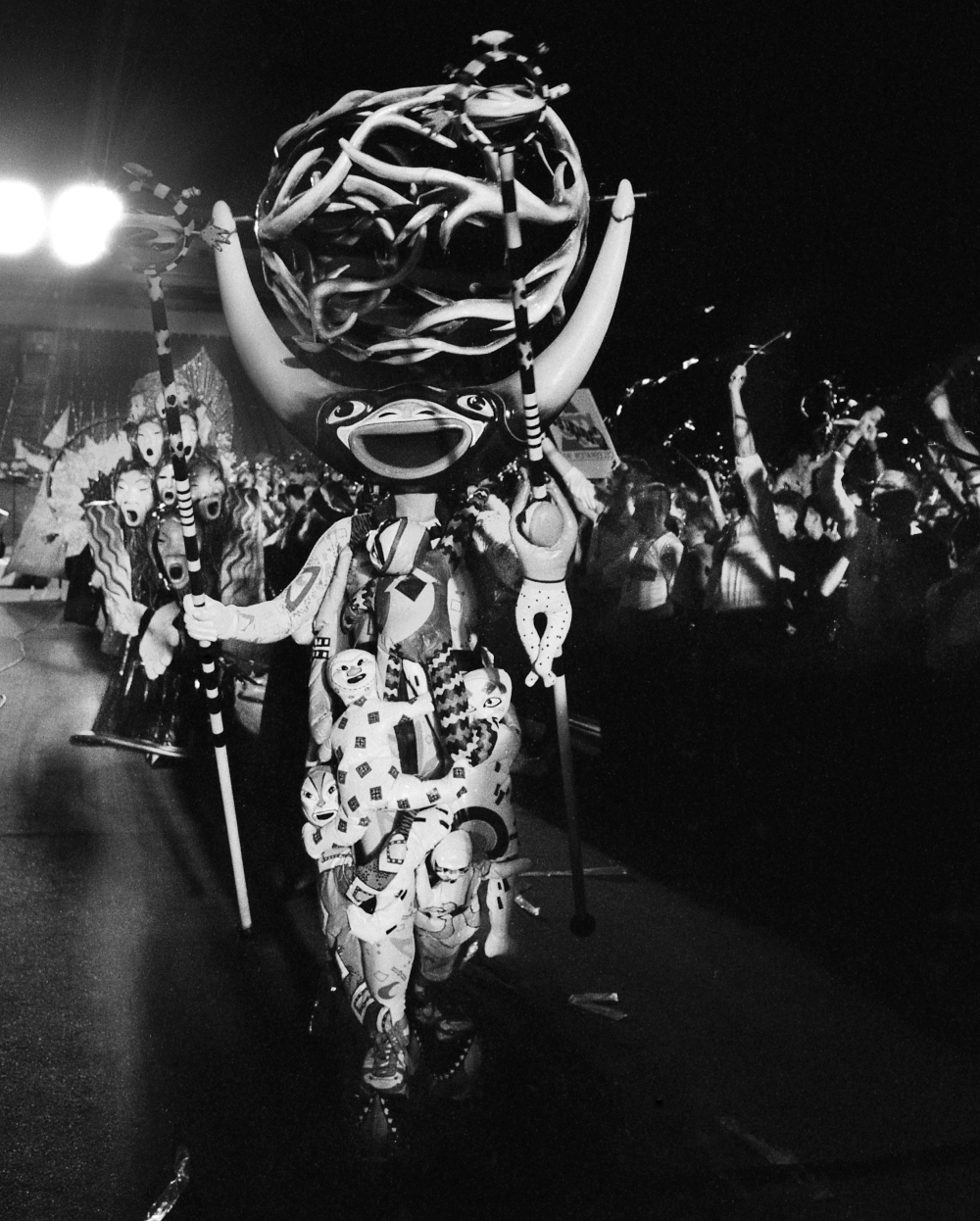 Black and white photo of a character in the Carnaval! fantasy parade. The patterned costume has several three-dimensional baby-sized fabric dolls attached to it. The character has a decorated staff in each hand. One has a baby-sized wood doll clinging to it. The character wears a glossy, painted, wooden mask. It has a wide, open smile and long horns with a large orb-shaped 'crown' comprised of intertwining curved branch-like structures between them.