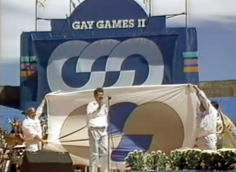 At the Closing Ceremonies of Gay Games II, Richard Dopson stands on the stage at the microphone in front of a large Gay Games flag held out by the Vancouver delegation.