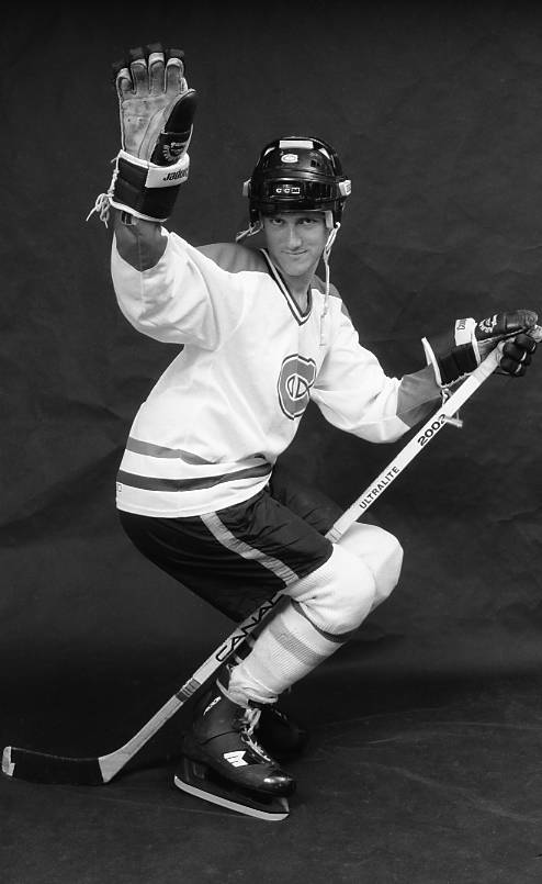Black and white studio photograph of a male hockey player wearing a Montreal Canadiens white jersey and smiling flirtatiously while posing as if 'riding' his stick.