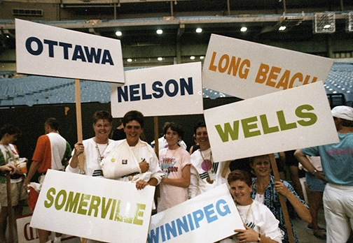 A group of Canadian female athletes hold signs with the names of their hometowns on the floor at B.C. Place Stadium during Closing Ceremonies.