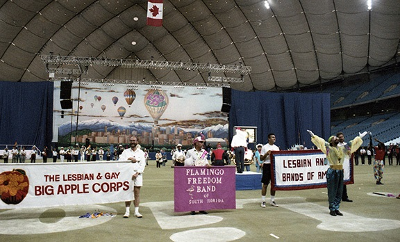 The Lesbian and Gay Bands of America perform on the floor of B.C. Place Stadium at the Closing Ceremonies. Banners for the Lesbian and Gay Big Apple Corps and the Flamingo Freedom Band dominate the foreground.