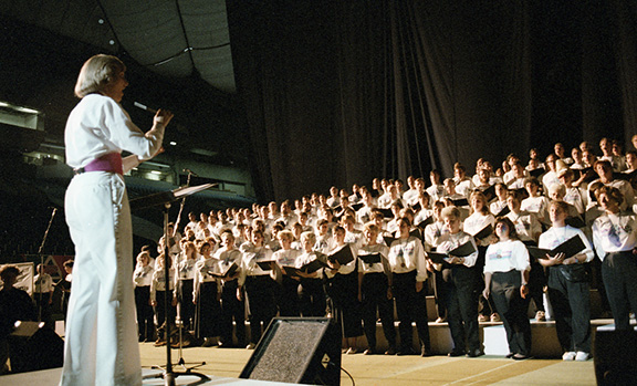 Over 70 members of the Celebration '90 Festival Chorus, in uniform black pants and white shirts, are assembled on a tiered riser on the stage at B.C. Place Stadium. Carole White conducts their vocal performance at the Closing Ceremonies.