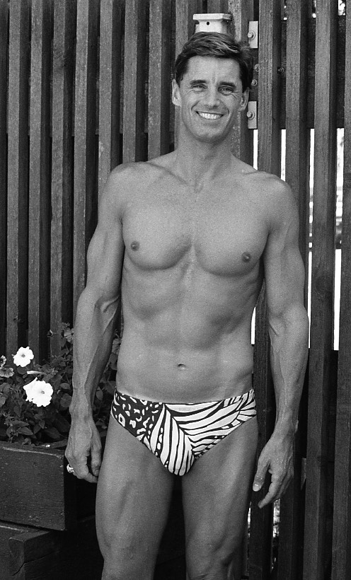 Black and white photo portrait of swimmer Michael Mealiffe. He is wearing swimming trunks and standing on an outdoor patio with a slat fence as background.