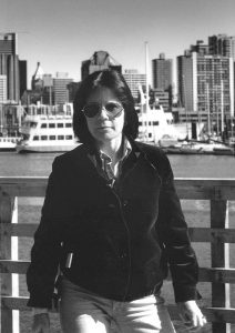 Black and white photo of Mary Anne McEwen on the Vancouver waterfront with the city behind her, c.1983.