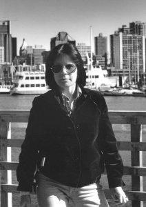 Photo en noir et blanc de Mary Anne McEwen sur le front de mer de Vancouver avec la ville derrière elle, vers 1983.