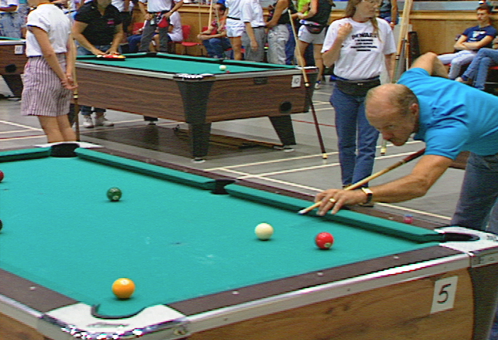 Man lines up a shot at Billiards competition.