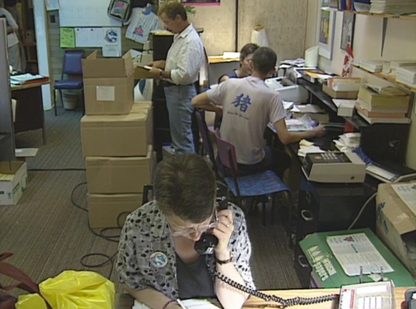 Four volunteers and staff busy working in a crowded Celebration '90 Office at Enterprise Hall the day before registration opens.
