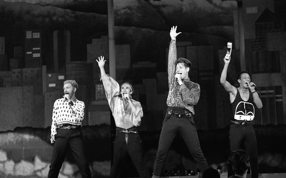 A black and white photo of the four male members of the Canadian a cappella group, The Nylons, striking a pose - wide leg stance, mic in one hand, and the other held straight up towards the roof - as they perform on the B.C. Place Stadium stage for Closing Ceremonies.