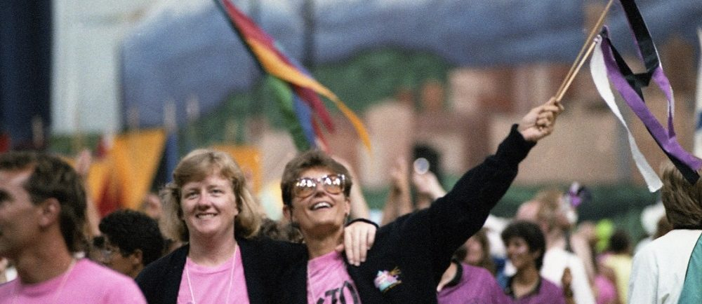 A group of female athletes dressed in pink t-shirts and black jackets smile and wave to the crowd with colourful streamers as they walk in the parade of athletes at Opening Ceremonies. The gigantic mural of Vancouver that backed the stage is visible in the background.