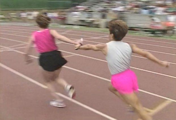 Two women pass the baton in women's relay race at Swanguard Stadium, Burnaby.